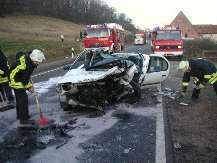 Nach den Rettungsarbeiten reinigen die Einsatzkräfte die Unfallstelle und beseitigen Autoteile von der Fahrbahn. In dem Fahrzeug (Bildmitte) war ein Mann eingeklemmt.