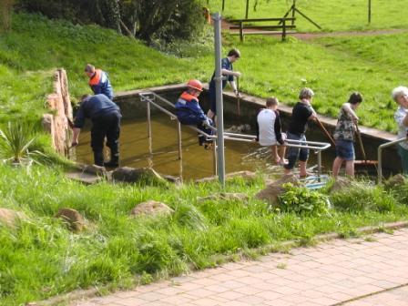 Mit Besen werden die letzten Algen- und Moos-Reste aus dem Kneipp-Becken beseitigt.