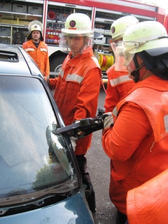 Mit einem Schneidgerät (Schere) trennt ein Feuerwehrangehöriger die so genannte A-Säule des Übungsfahrzeuges durch.