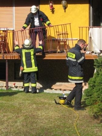 Im Hintergrund heben zwei Feuerwehrmänner das herausgeschnittene Balkonteil heraus. Im Vordergrund mit Handfunkgerät: Wehrführer Otterberg, Hendrik Braun.