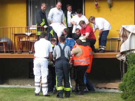 Rettungsdienstpersonal und Feuerwehrkräfte heben zusammen den Patienten auf die Trage.
