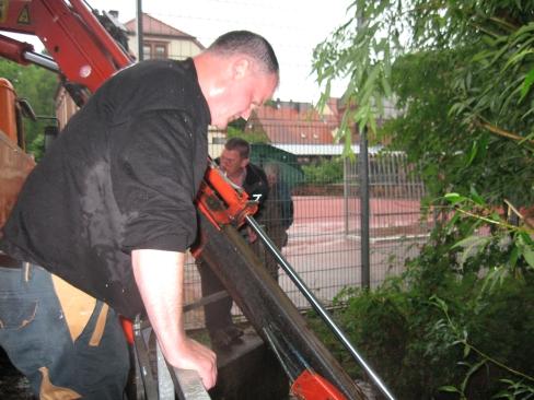 Zwei Mitarbeiter des Bauhofs während den Arbeiten. Hinter dem Gitterzaun Bürgermeister Ulrich Wasser.