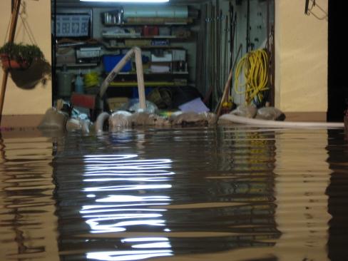 Eine Sandsackbarriere vor einer Garage. Eine Tauchpumpe befördert eingedrungenes Wasser nach draußen.