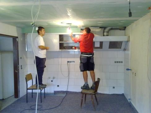 Zwei Wehrleute installieren die Kücheneinrichtung.