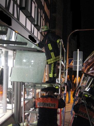 Eigentumssicherung in Otterberg. Die Wehrleute entfernen vor einem Bekleidungsgeschäft die Glasplatten über dem Gehweg.