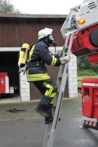 Feuerwehrmann mit Atemschutzgerät besteigt Drehleiter
