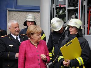 Bundeskanzlerin Angela Merkel unterhält sich in Bonn mit ehrenamtlichen Feuerwehrangehörigen, die ihr gemeinsam mit Hans-Peter Kröger, Präsident des Deutschen Feuerwehrverbandes (DFV), die Einsatzmöglichkeiten eines Löschgruppenfahrzeugs für den Katastrophenschutz demonstrieren. (Foto: Friedrich Kulke/DFV)