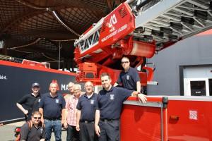 Angehörige der Feuerwehr Otterbach vor der mit 68 Metern Länge derzeit größten Drehleiter der Welt.