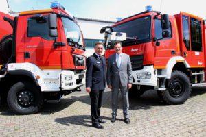 DFV-Präsident Ziebs (links) und BBK-Präsident Unger (rechts) vor zwei Katastrophenschutzfahrzeugen. Quelle: Lechner / BBK