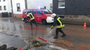 Feuerwehrkräfte reinigen die Hauptstraße in Hirschhorn von Schlamm und Geröll.