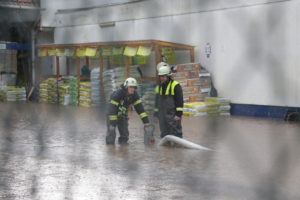 Zwei Feuerwehrangehörige bringen am 28. Mai 2016 auf dem Gelände des Baumarkts in Otterberg eine Pumpe in Stellung.