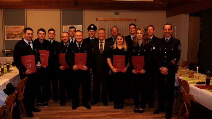 Die beförderten und geehrten Feuerwehrangehörigen mit Wehrführung, Wehrleitung und Stadtbürgermeister Martin Müller (mitte).